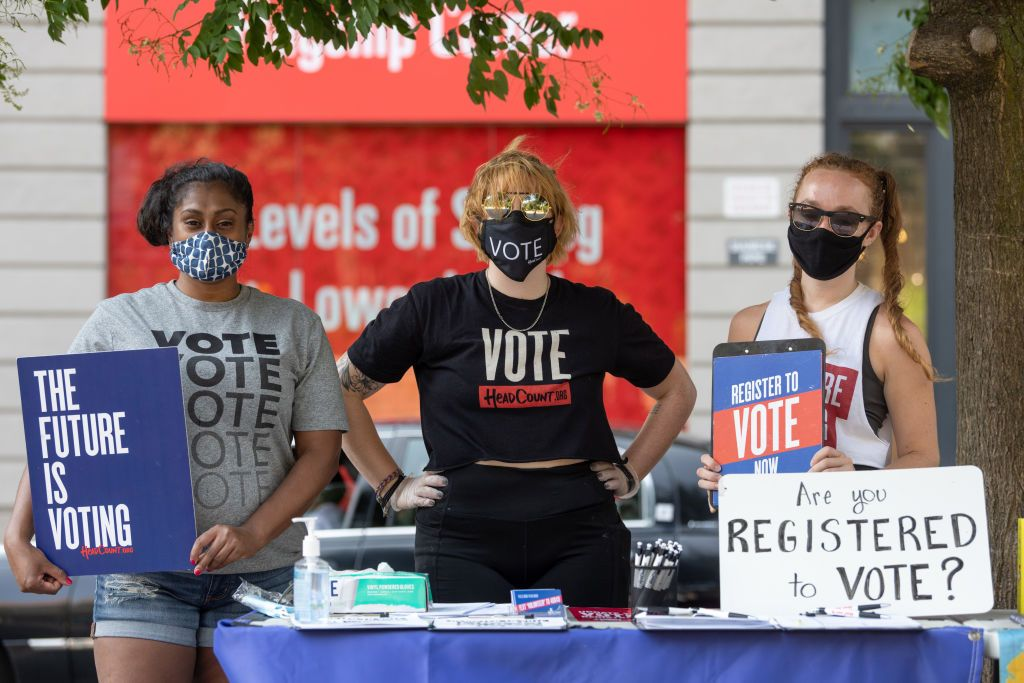 women-wearing-masks-pose-behind-a-voter-registration-table-news-photo-1597785577-2